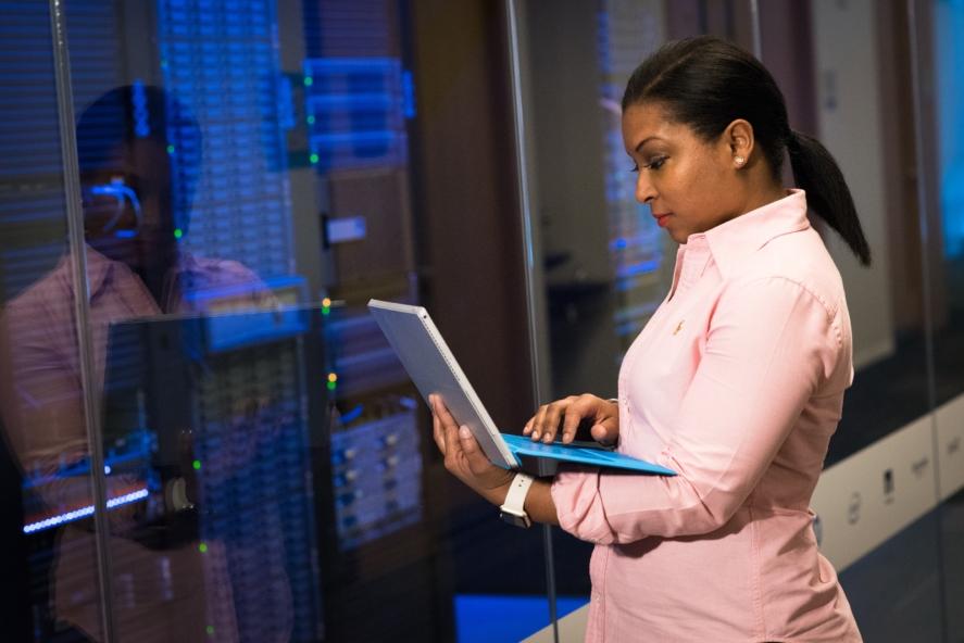 szerver hosting, hölgy géppel a kezében szerverek előtt